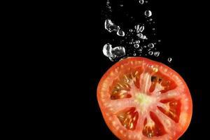 Tomatenscheibe, die in Wasser am schwarzen Hintergrund fällt foto