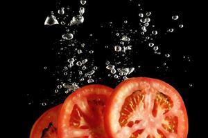 Tomatenscheiben fallen in Wasser bei schwarzem Hintergrund foto