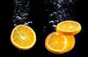Orangenscheibe im Wasser mit Blasen