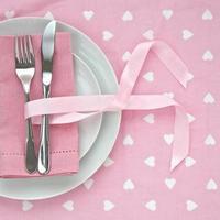 Messer und Gabel mit rosa Tischdekoration zum Valentinstag