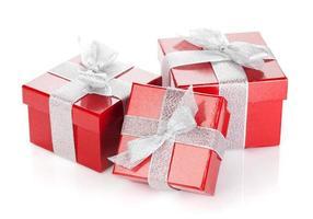 drei rote Geschenkboxen mit silbernem Band und Schleife