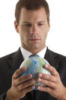Geschäftsmann hält Globus