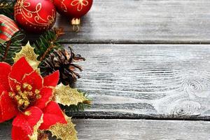 rote Weihnachtskugeln mit Schleifen auf einem Holzbrett