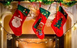 Drei Weihnachtsstrümpfe hängen am verzierten Kamin foto