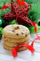 Kekse mit Schokolade mit Weihnachtsbaumzweigen und Dekorationen