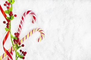 zwei Zuckerstangen mit Weihnachtsdekoration auf schneebedecktem Hintergrund
