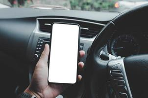 Mann hält das Telefon im Auto