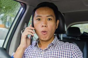 schockierter Mann, der im Auto telefoniert