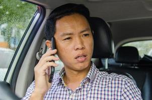 asiatischer Mann, der im Auto am Telefon spricht