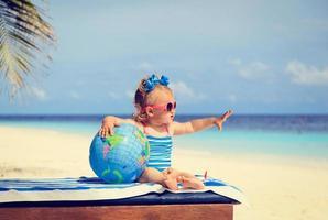 kleines Mädchen mit Globus und Spielzeugflugzeug am Strand