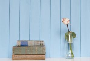 Bücherstapel und weiße Rose in der Flasche foto