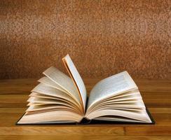 altes offenes Buch auf Grunge-Holztisch