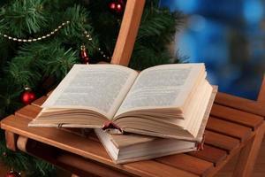 Komposition mit Büchern auf Stuhl auf Weihnachtsbaumhintergrund foto
