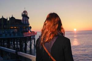 Frau, die das Meer bei Sonnenuntergang bewundert foto