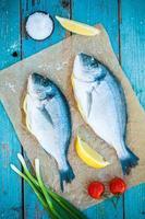 zwei rohe Dorado-Fische mit Zitrone, Frühlingszwiebeln und Tomaten