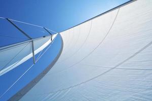 einzelnes Segel mit der Sonne dahinter, verbunden mit dem Mast foto