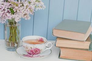 Haufen Flieder, Bücher und Teetasse