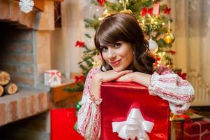 Weihnachtsfrauenporträt halten rotes Weihnachtsgeschenk über Wohnzimmer