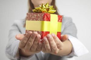 Geschäftsfrau hält Geschenk.