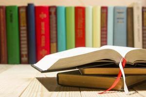 offenes Buch, gebundene Bücher auf Holztisch foto
