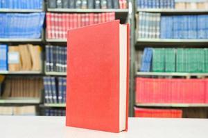 rotes Buch, das auf Tisch mit Bücherregal im Hintergrund steht