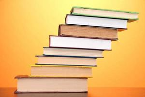 Stapel interessanter Bücher und Zeitschriften auf farbigem Hintergrund