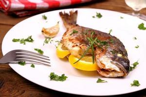 Gegrillter Seebrassenfisch, Zitrone auf weißem Teller