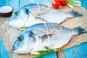 zwei rohe Dorada-Fische mit Zitrone, Frühlingszwiebeln, Kirschtomaten