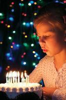 Mädchen bläst Kerzen auf dem Kuchen aus foto