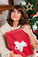 Weihnachtsfrauenporträt halten rotes Weihnachtsgeschenk über Wohnzimmer foto