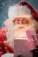 glücklicher Weihnachtsmann, der sein Weihnachtsgeschenk am Nordpol öffnet foto