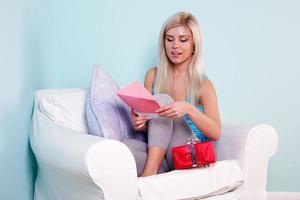 blonde Frau, die eine Geburtstagskarte öffnet