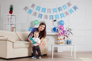 Porträt von Mutter und Baby mit Geburtstagstorte foto