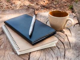 Kaffeetasse und Buch auf Holz breit