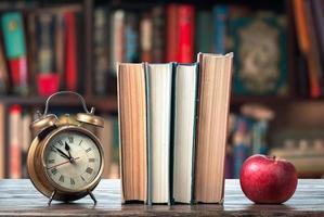Buch, Apfel und Wecker foto