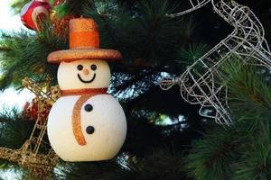 Schneemann, der am Weihnachtsbaum hängt.