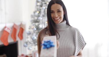 lächelnde junge Frau, die ein Weihnachtsgeschenk heraushält