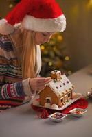 glückliches Mädchen im Weihnachtsmannhut, das Weihnachtsplätzchenhaus verziert