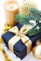goldene Weihnachtskomposition mit Geschenkbox, Kerze und Zweig von
