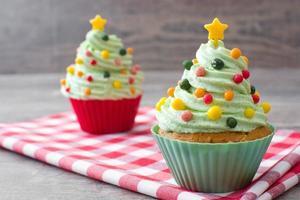 Cupcakes mit Weihnachtsbaumform auf Holz foto