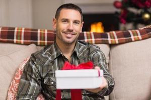 lächelnder Mann, der Geschenk am Weihnachtstag anbietet