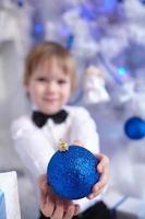 Junge in Hemd und Fliege schmückt einen Weihnachtsbaum