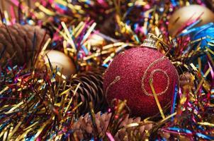Weihnachtskugel und Zapfen in mehrfarbigem Lametta
