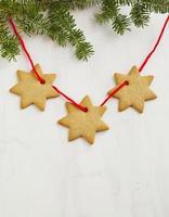 Lebkuchenplätzchen hängen am Weihnachtsbaumzweig