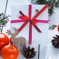 Weihnachtsgeschenke mit rotem Band und Mandarinen, dekorativ de
