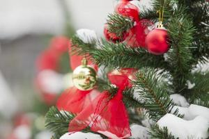 Weihnachtskugeln hängen an einem schneebedeckten Weihnachtsbaum