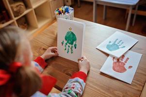 Kindermädchen im Weihnachtspullover, der Handabdruckpostkarten macht foto