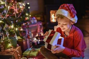 Weihnachtszeit, kleiner Junge öffnet ein Geschenk in der Nähe von Baum beleuchtet