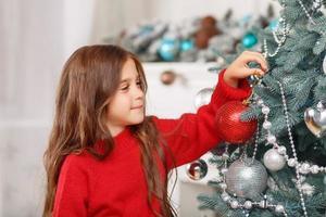 nettes Mädchen, das nahe Weihnachtsbaum spielt
