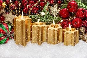 Adventsdekoration mit vier brennenden goldenen Kerzen